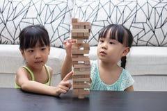 Irmãs mais nova chinesas asiáticas que jogam pilhas de madeira fotos de stock