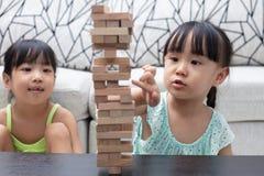 Irmãs mais nova chinesas asiáticas que jogam pilhas de madeira foto de stock