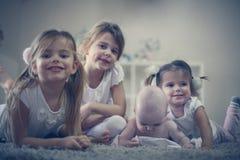 Irmãs mais nova com poses do irmão do bebê à câmera Imagem de Stock Royalty Free