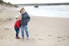Irmãs mais nova de Twi na praia no outono Fotos de Stock Royalty Free