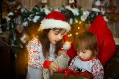 Irmãs mais nova nos pijamas na Noite de Natal fotos de stock royalty free