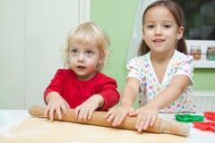 Irmãs no bolo do cozimento da cozinha Imagem de Stock