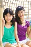 Irmãs que apreciam o balanço do rattan Imagem de Stock Royalty Free