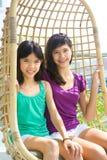 Irmãs que apreciam o balanço do rattan Imagens de Stock