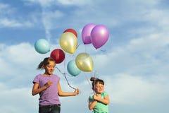 Irmãs que correm com balões fotos de stock royalty free
