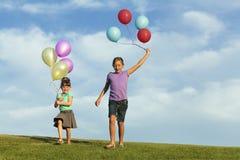 Irmãs que correm com balões foto de stock