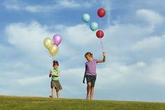 Irmãs que correm com balões imagens de stock
