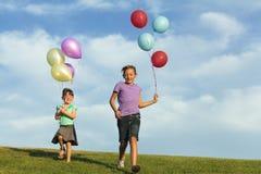 Irmãs que correm com balões imagem de stock