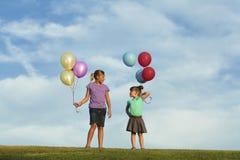 Irmãs que correm com balões imagem de stock royalty free