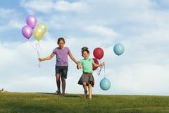Irmãs que correm com balões fotos de stock
