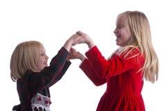 Irmãs que dançam em vestidos do Natal Imagens de Stock Royalty Free