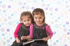 Irmãs que guardam o livro imagens de stock royalty free
