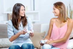 Irmãs que jogam jogos de vídeo na sala de visitas imagem de stock
