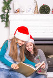 Irmãs que leem uma história do Natal Fotos de Stock