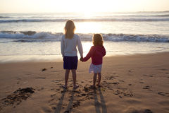 Irmãs que prendem as mãos na praia Fotografia de Stock Royalty Free