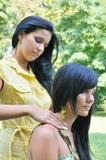 Irmãs - uma dá a massagem da garganta a outra Foto de Stock