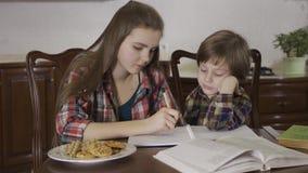 Irm? que ajuda seu irm?o com atribui??o home Retrato de duas crianças bonitos que trabalham em trabalhos de casa junto filme