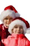 Irmão e irmã que desgastam chapéus de Santa.   Fotos de Stock