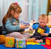 Irmão e irmã que jogam com cubo colorido Foto de Stock