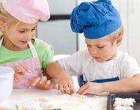 Irmão novo e irmã que amassam uma massa de pão Fotos de Stock Royalty Free