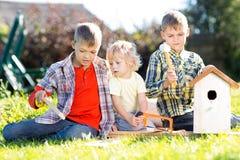 Irmãos de crianças que fazem a caixa de assentamento junto Imagem de Stock Royalty Free