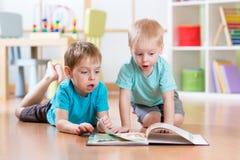 Irmãos felizes dos meninos das crianças que leem a enciclopédia junto em casa Imagem de Stock