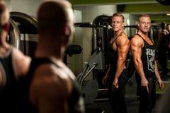 Irmãos gêmeos que olham no espelho após o exercício do body building em f Fotos de Stock Royalty Free