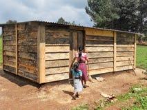 Irmãs que andam na casa da América Central rural para limpar Imagens de Stock