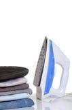 Iron. Neatly stacked laundry pants with iron box Stock Photo