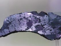 Iron alien meteorite with Widmanstatten pattern on light royalty free stock photo
