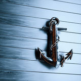 Iron anchor on a background of black painted wood 3d render.  Stock Photo