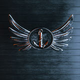 Iron anchor on a winged emblem on a background of black painted. Wood 3d render Stock Image