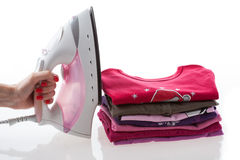 Iron and arranged clothes Stock Photo
