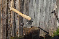 Iron ax with a wooden handle in a tree deck. Stump giving summer in the background of a green grass glade sunny day stock photos