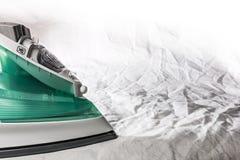 Iron on background crumpled tissue and ironing. Modern steam iron and ironing on crumpled tissue Stock Photos