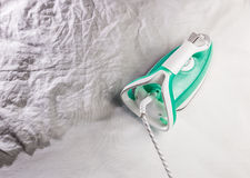Iron on background crumpled tissue and ironing. Modern steam iron and ironing on crumpled tissue Stock Images