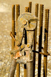 Iron bar cutter. A worn iron bar cutter leaning against concrete reinforcement steel bars stock photos