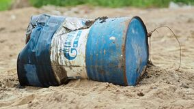 SAINT PETERSBURG, Russia, June 20, 2020. Rusty barrel of Gazpromneft or Gazprom lies in sand