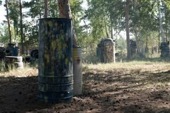Iron barrels in the foreground with multi-colored blots and smudges from shots from the paintball weapon. Old tires from a car and. Trees. Paintball territory stock photo