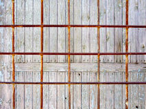 Iron bars. Rusty iron bars against a wooden fence Royalty Free Stock Photos