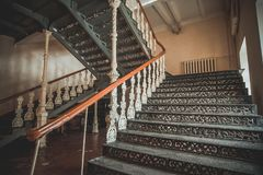 Iron beautiful vintage stairs in the old mansion. Ornate handrail of wrought iron.  royalty free stock photography