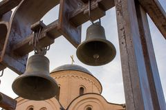 Iron bells on front and dome of the church with cross on the back remote background. Religious photo of the old neighborhood of Po Stock Photos