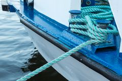 Iron Berth Holding White Boat Lines. On a White and Blue Boat Near Shore Royalty Free Stock Images