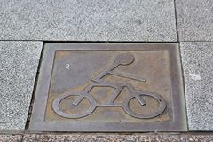 Iron bicycle sign on walk way Stock Photography