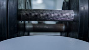 Iron black equipment for real gym guy. Two dumbbells are on stand and waiting for athlete to exercise with it stock video footage