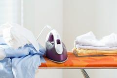 Iron on a board. New shining iron on an orange ironing board Royalty Free Stock Photos