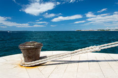 Iron bollard with white, thick hawser. Iron bollard with attached hawser on quay in port in Zadar in Croatia Stock Images