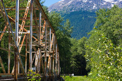 Iron Bridge Alaska. Scenic view of mountains from weather-worn iron bridge. This is a Rigid-Frame Bridge in which the superstructure and substructure are rigidly stock image