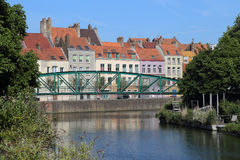 Canal and historical houses in old Dunkirk, France. The iron bridge Passerelle de la Douane across a canal and historical houses along the Quay de la Concorde Stock Image