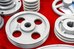 Iron casting industrial parts pulley for transmission power to automotive engine pump or blower casting by green sand or shell. Mold process on red table stock photo